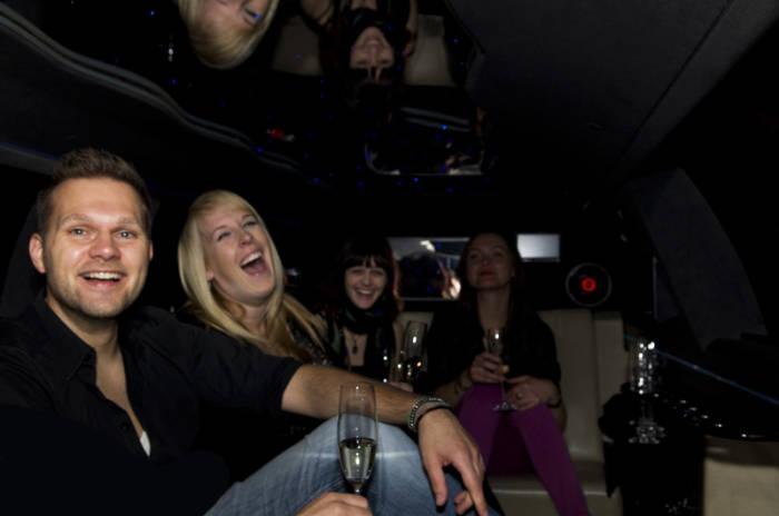 Drei lachende Frauen  und ein Mann mit Sekt in einer Limousine