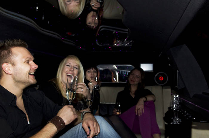 In einer Limousine stoßen die Gäste mit Sekt an.