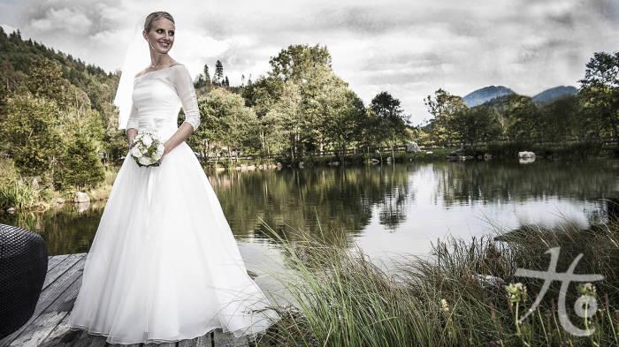 Braut im weißen Kleid vor einem grünenSee