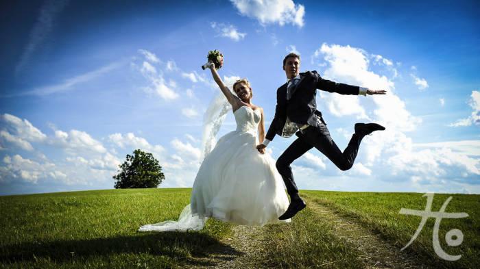 Braut und Bräutigam beim Luftsprung fotographiert