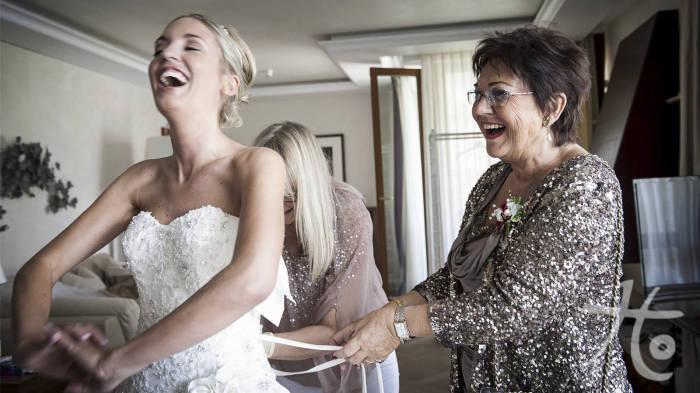Braut beim Ankleiden mit ihrer Mutter