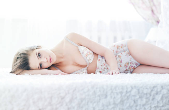 Frau in Blumendessous lieg auf Bett
