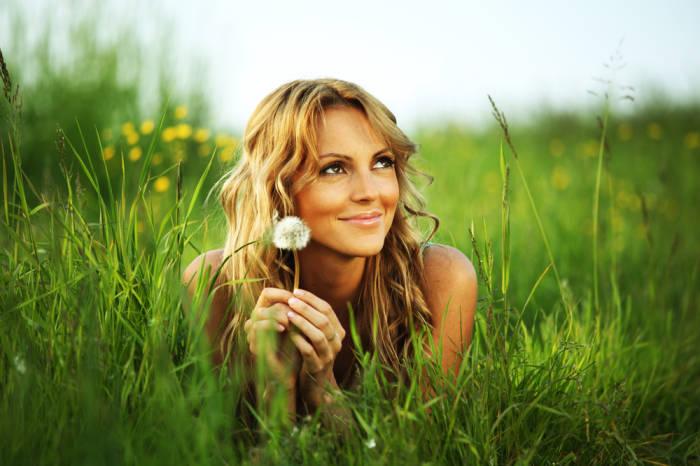 blonde Frau liegt in grüner Wiese und lächelt