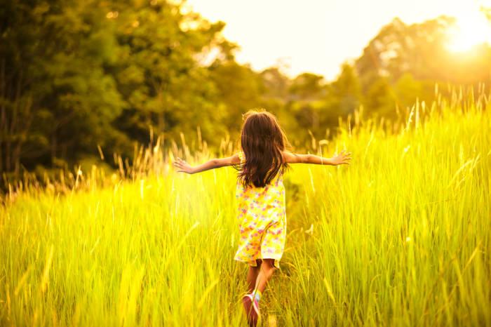 Kind läuft durch hohes Gras