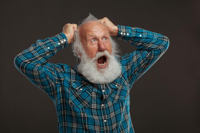 Alter, bärtiger Mann rauft sich die Haare