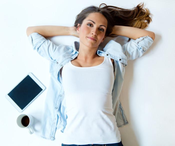 Porträt einer jungen Frau, die auf dem Rücken liegt