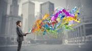 Mann in Anzug mit Laptop, aus dem Farben explodieren