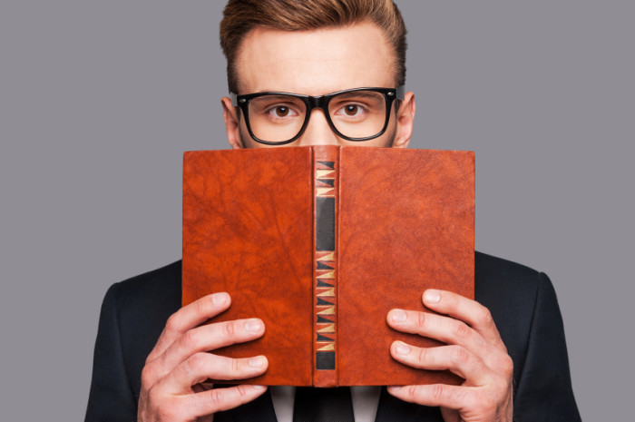 More knowledge!  Young man in formalwear hiding his face behind a book while standing against grey background