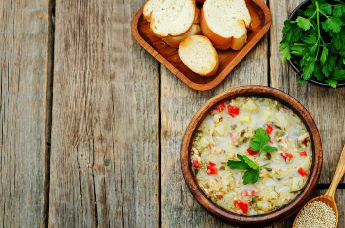 milk soup with potatoes, quinoa and peppers on a dark wood background. the toning. selective focus