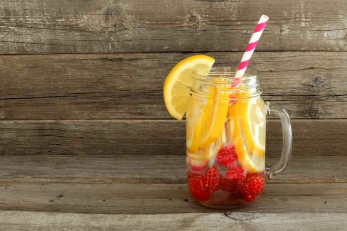 Detox water with lemon and raspberries in a mason jar with straw against a wood background