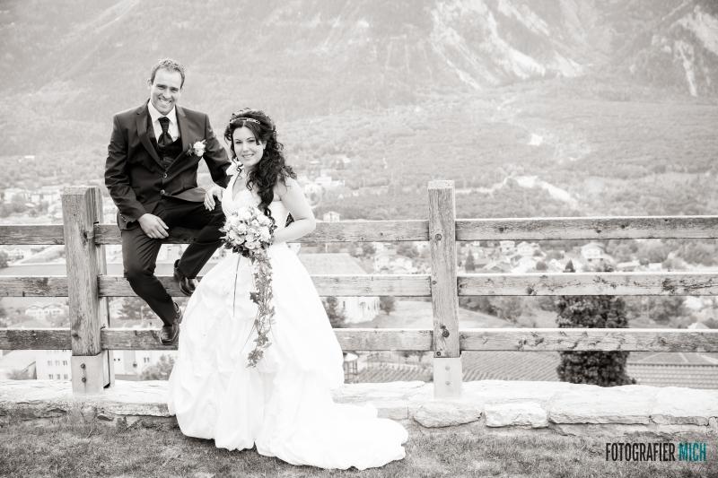 Das glückliche Paar posiert vor einem Schweizer Dorf.